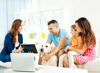 Young couple with their toddler and dog sitting on a couch going over something on a tablet with an agent